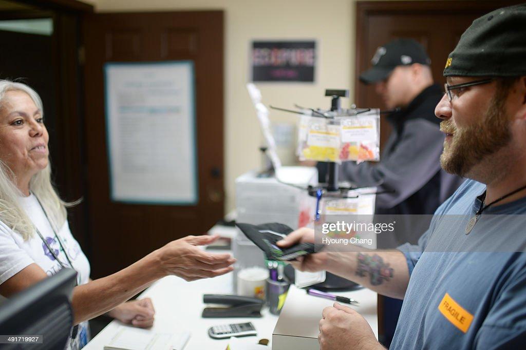Lorraine Cendejas of Botana Care, left, helps John Hartlauer of Northglenn purchasing recreational marijuana. Northglenn, Colorado. May 16. 2014.
