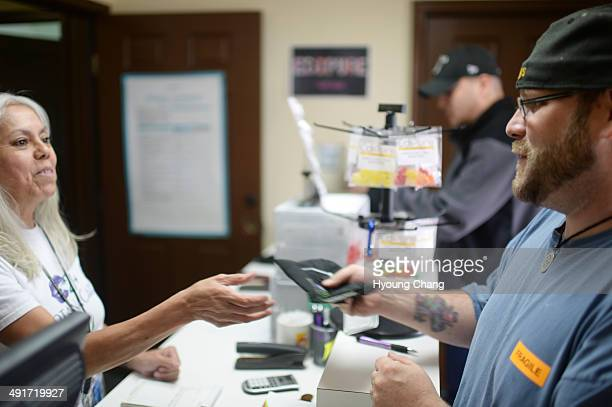 Lorraine Cendejas of Botana Care left helps John Hartlauer of Northglenn purchasing recreational marijuana Northglenn Colorado May 16 2014
