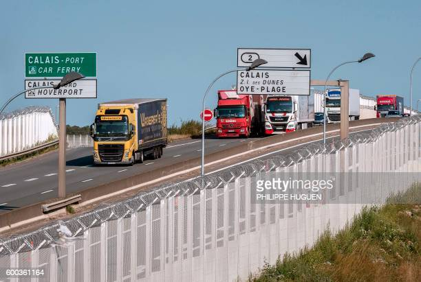 Lorries drive along a protection fence preventing access to a circular road leading to the port of Calais next to the 'Jungle' migrant camp in Calais...