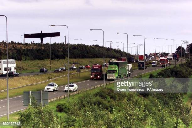 Lorries pass the sculpture Angel of the North as they drive slowly along the A1 near Gateshead Tyne and Wear blocking the road in protest against...