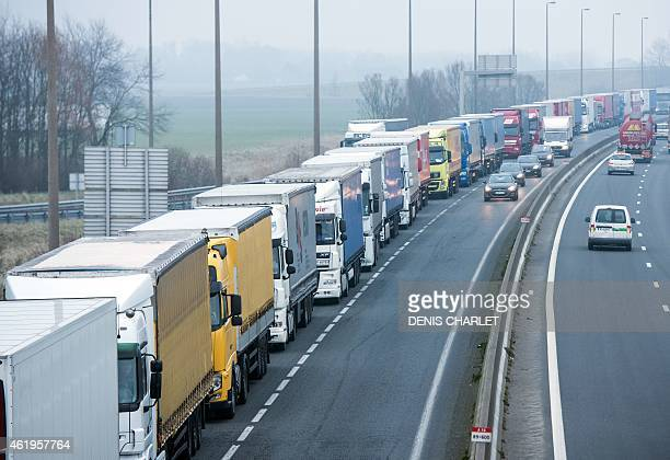 Lorries sit in the emergency lane on the A16 motorway leading to the port of Calais northern France on January 22 as traffic is stopped while repairs...