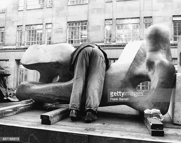 Lorry driver Ernie Saunders leaning over a Henry Moore sculpture to untie it from its transport outside Christie's London January 1st 1973