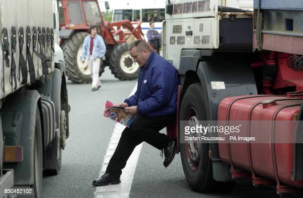 Lorry driver Gary McRobbie from Aberdeen reads as he waits to get back to Britain through the Channel Tunnel while stuck in Calais after French...