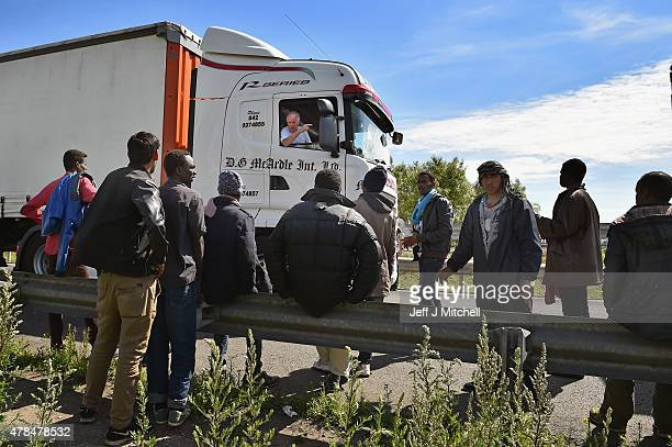 A lorry driver gestures at migrants as they continue to try and board lorries bound for the United Kingdom on June 25 2015 in Calais France Many...