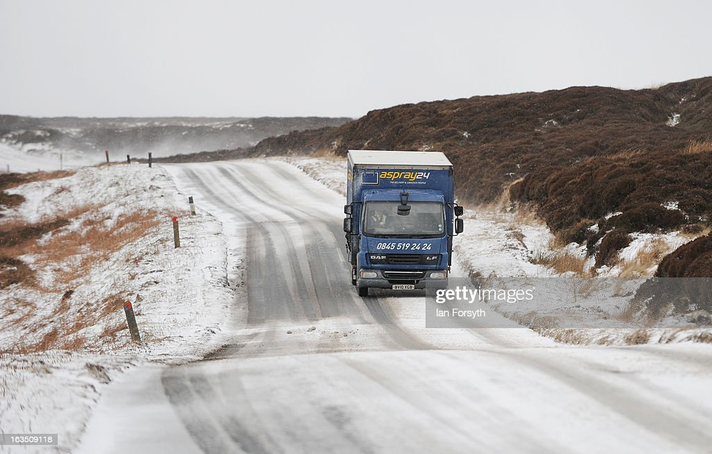 A lorry driver makes his way along a snow covered road as brief but heavy snow storms move across the Yorkshire Moors on March 11, 2013 in Yorkshire, United Kingdom. Wintery weather returned to the UK as snow fell across many parts of the country, with a number of weather warnings being issued.