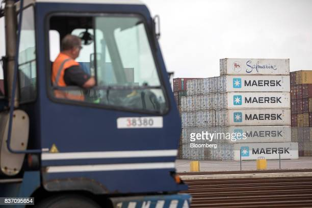 A lorry driver waits to load cargo as shipping containers bearing the AP MollerMaersk A/S logo sit beyond at the Port of Felixstowe Ltd a subsidiary...