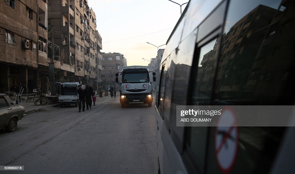 A lorry the Syrian Arab Red Crescent containing aid parcels from arrives on February 13, 2016 in the rebel-held city of Douma, northeast of the capital Damascus. A convoy of the Syrian Red Crescent entered the besieged rebel-controlled Douma area bringing medicines and also milk for children, said Syrian Red Crescent director of operations Hazem Bakla. / AFP / Abd Doumany