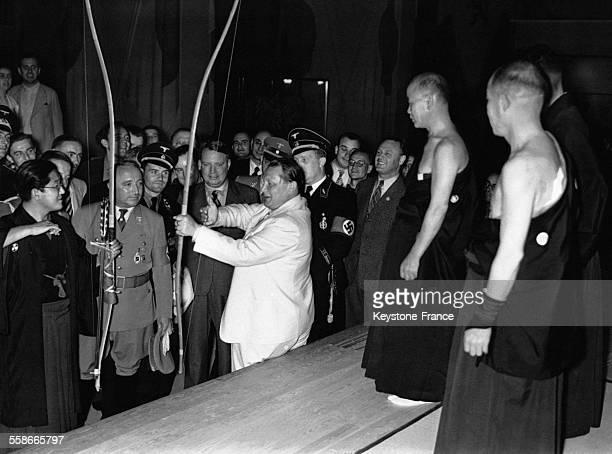Lors de sa visite à la foire internationale de l'artisanat Hermann Goering tend un arc devant la délégation japonaise avant de décocher une flèche le...