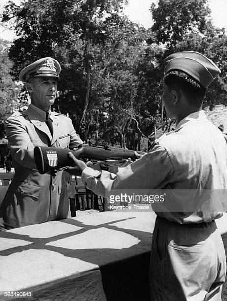 Lors d'une cérémonie un officier de l'armée américaine remet un fusil orné d'un blason sur la crosse à un soldat de l'armée du Laos à Vientiane Laos...