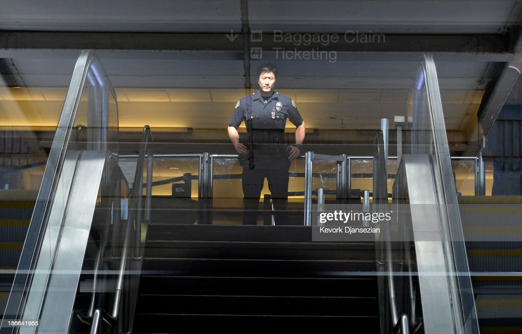 A Los Angeles Airport Police officer stands in front of Terminal 3 security screeners, the site of shooting scene, after law enforcement official completed their investigation and prepare to re-open the terminal at Los Angeles International Airport November 2, 2013 in Los Angeles, California. The airport is almost back to normal operations a day after a man pulled an assault rifle and shot his way through security at Terminal 3, killing one Transportation Security Administration worker and wounding several others. Federal officials identified the alleged gunman as Paul Ciancia, 23, of New Jersey.