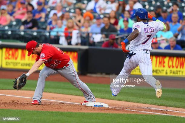Los Angeles Angels first baseman CJ Cron misses first base and New York Mets third baseman Jose Reyes is safe during the Major League Baseball game...