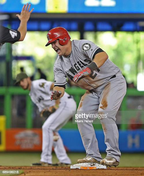 Los Angeles Angels' Mike Trout grimaces after hurting his hand sliding safely into second base during the fifth inning against the Miami Marlins on...