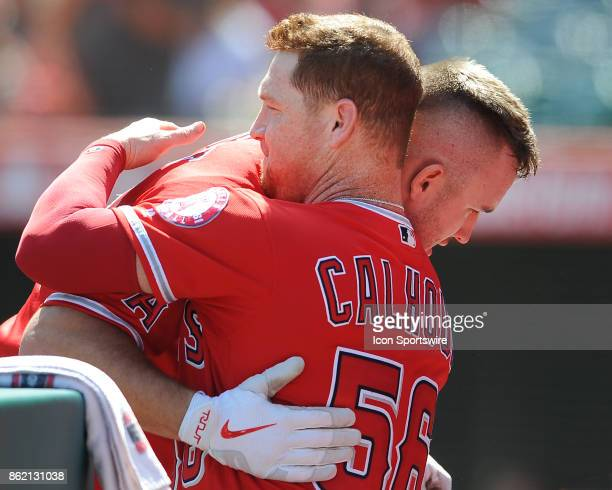 Los Angeles Angels of Anaheim center fielder Mike Trout hugs left fielder Kole Calhoun after Trout was pulled from the game in the fourth inning of a...