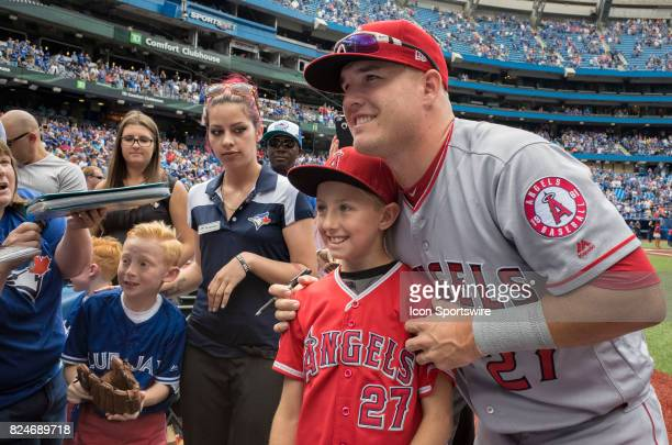 Los Angeles Angels of Anaheim Center fielder Mike Trout poses with a young fan he helped over the fence before the regular season MLB game between...
