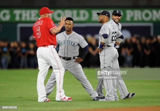 Los Angeles Angels of Anaheim designated hitter Albert Pujols talks with Seattle Mariners shortstop Jean Segura second baseman Robinson Cano and...