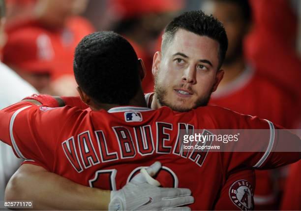 Los Angeles Angels of Anaheim first baseman CJ Cron gets a hug in the dugout from third baseman Luis Valbuena after Cron hit a two run home run in...