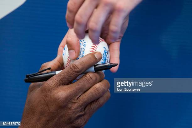 Los Angeles Angels of Anaheim infield coach Alfredo Griffin hands a ball he just autographed to a fan before the regular season MLB game between the...
