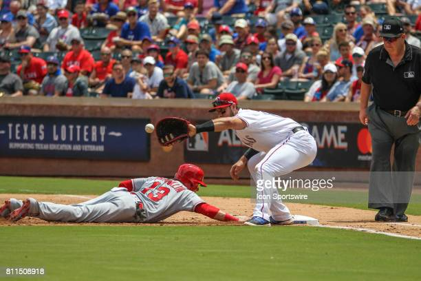Los Angeles Angels of Anaheim infielder Nick Franklin dives to avoid a tag by Texas Rangers first baseman Joey Gallo during the game between the Los...