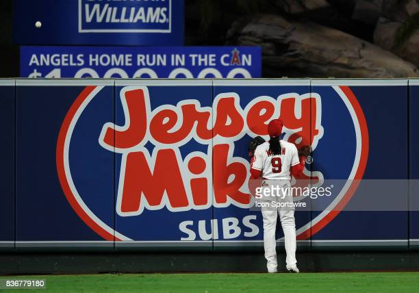 Los Angeles Angels of Anaheim left fielder Cameron Maybin faces the outfield wall while a ball hit by Texas Rangers third baseman Adrian Beltre heads...
