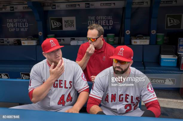 Los Angeles Angels of Anaheim Pitcher Brooks Pounders sits in the dugout with teammate Kaleb Cowart as the trainer applies lip balm before the...