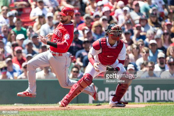 Los Angeles Angels second baseman Kaleb Cowart slides safely into home to score past Boston Red Sox catcher Christian Vazquez in the second inning...