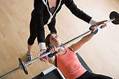 Los Angeles, California, USA, Woman lifting barbell while instructor assisting her