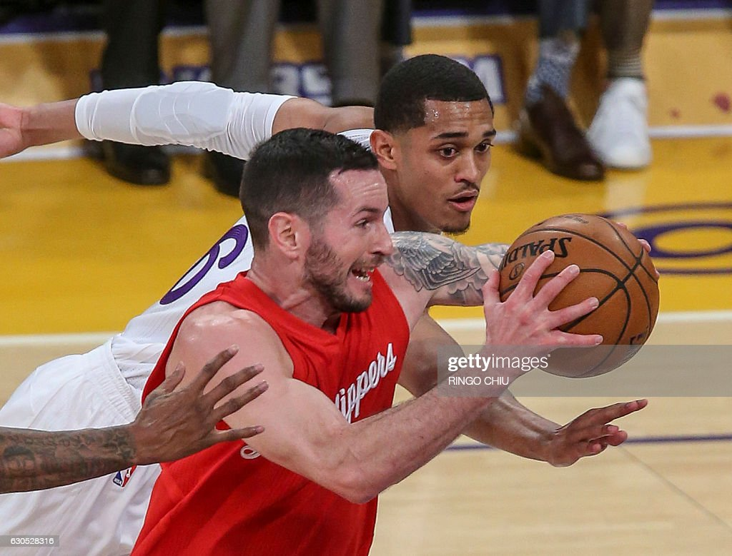 Los Angeles Clippers guard J.J. Redick (#4) drives between Los Angeles Lakers guards Jordan Clarkson (#6) during their NBA game at Staples Center in Los Angeles, California on December 25, 2016. / AFP / RINGO