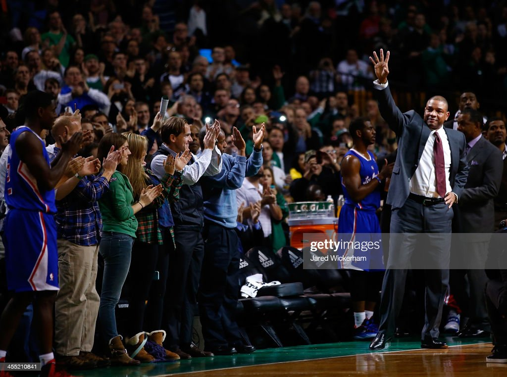 Los Angeles Clippers head coach, <a gi-track='captionPersonalityLinkClicked' href=/galleries/search?phrase=Doc+Rivers&family=editorial&specificpeople=206225 ng-click='$event.stopPropagation()'>Doc Rivers</a>, acknowledges the crowd at the end of the first quarter against his former team, the Boston Celtics, following a video tribute at TD Garden on December 11, 2013 in Boston, Massachusetts.