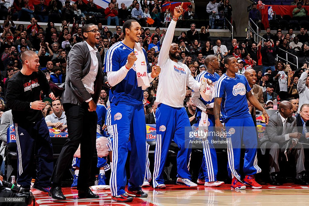Los Angeles Clippers players, from left, Trey Thompkins #33, Ryan Hollins #15, Ronny Turiaf #21, and Eric Bledsoe #12 celebrate from the bench as their teammates play the Sacramento Kings at Staples Center on December 21, 2012 in Los Angeles, California.