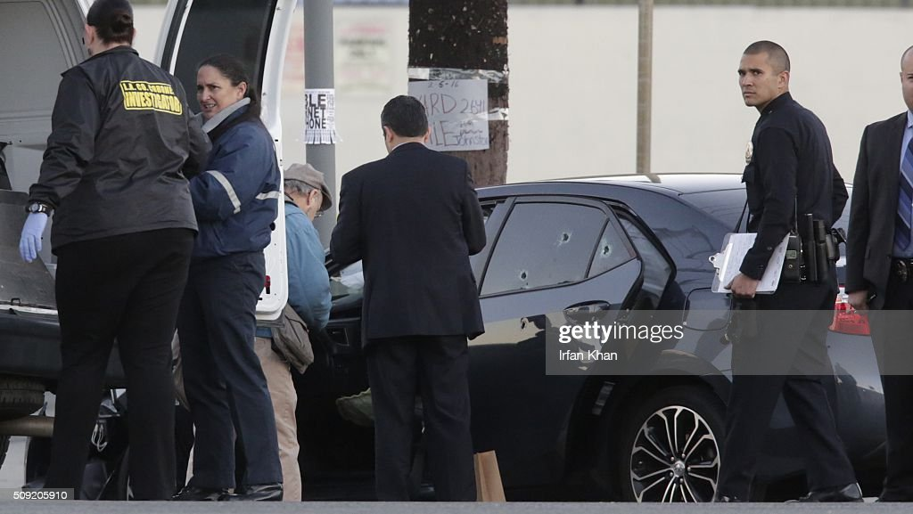 CA FEBRUARY 9, 2016 -- Los Angeles County coroner investigators remove the body from a bullet riddled car with an Uber sticker near the intersection of Griffin Avenue and North Broadway in the Lincoln Heights area of Los Angeles Tuesday morning, February 9, 2016.