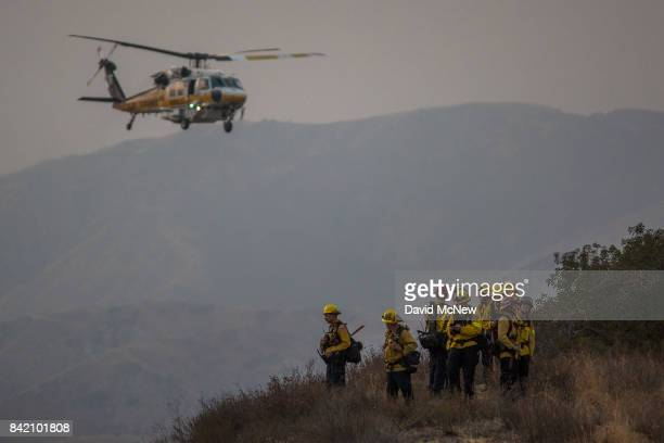 Los Angeles County Fire Department Firehawk helicopter flies past firefighters at the La Tuna Fire on September 2 2017 near Burbank California Los...