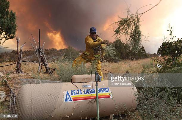 Los Angeles County firefighter clears brush away from a propane tank near a home as the Station Fire burns through the Angeles National Forest August...