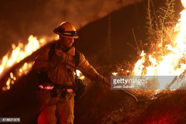 Los Angeles County firefighter monitors the Detwiler Fire on July 18 2017 in Mariposa California More than 1400 firefighters are battling the...
