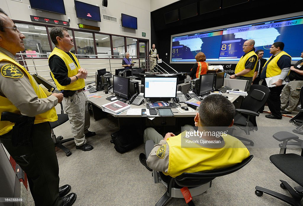Los Angeles County Sheriff Deputies and officials look at the large screen before taking cover as the California Integrated Seismic Network's Earthquake Ready Warning Demonstration System triggers an alarm for a simulated magnitude 7.0 aftershock following a simulated 7.8 magnitude earthquake during a functional exercise at the Los Angeles County Emergency Operations Center (CEOC) hosted by The County of Los Angeles Office of Emergency Management on March 21, 2013 in Los Angeles, California. The training exercise featured the California Integrated Seismic Network's Earthquake Ready Warning Demonstration System, which included 88 cities, 137 unincorporated communities, 200 schools and several nonprofit organizations.