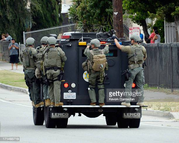 Los Angeles County Sheriff's SWAT team members standing on a armored car arrive to help Los Angeles Police Department officers during a massive...