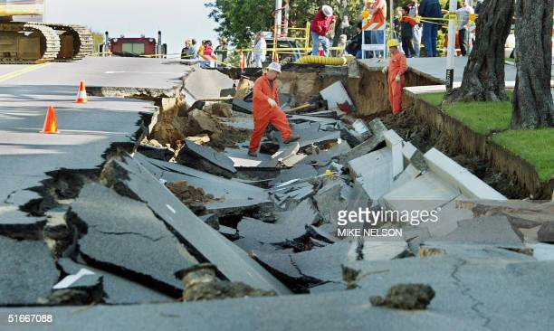 Los Angeles Department of Water and Power personnel inspect the damage done to Ocean Park Boulevard in Santa Monica after a broken water main...