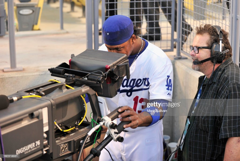 Los Angeles Dodger infielder <a gi-track='captionPersonalityLinkClicked' href=/galleries/search?phrase=Hanley+Ramirez&family=editorial&specificpeople=538406 ng-click='$event.stopPropagation()'>Hanley Ramirez</a> (L) tries out a video camera before the MLB game between the Colorado Rockies and Los Angeles Dodgers at Dodger Stadium on September 28, 2013 in Los Angeles, California.