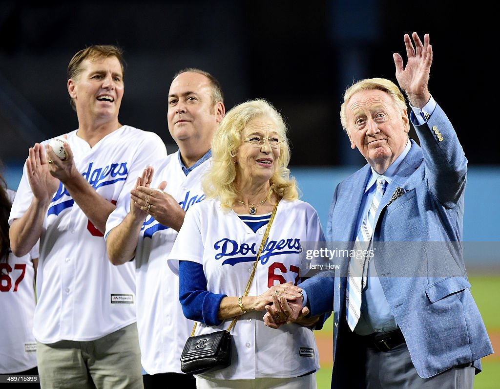 Los Angeles Dodgers broadcaster Vin Scully acknowledges applause from fans in front of wife Sandi Scully and sons Kevin Scully and Todd Scully before...