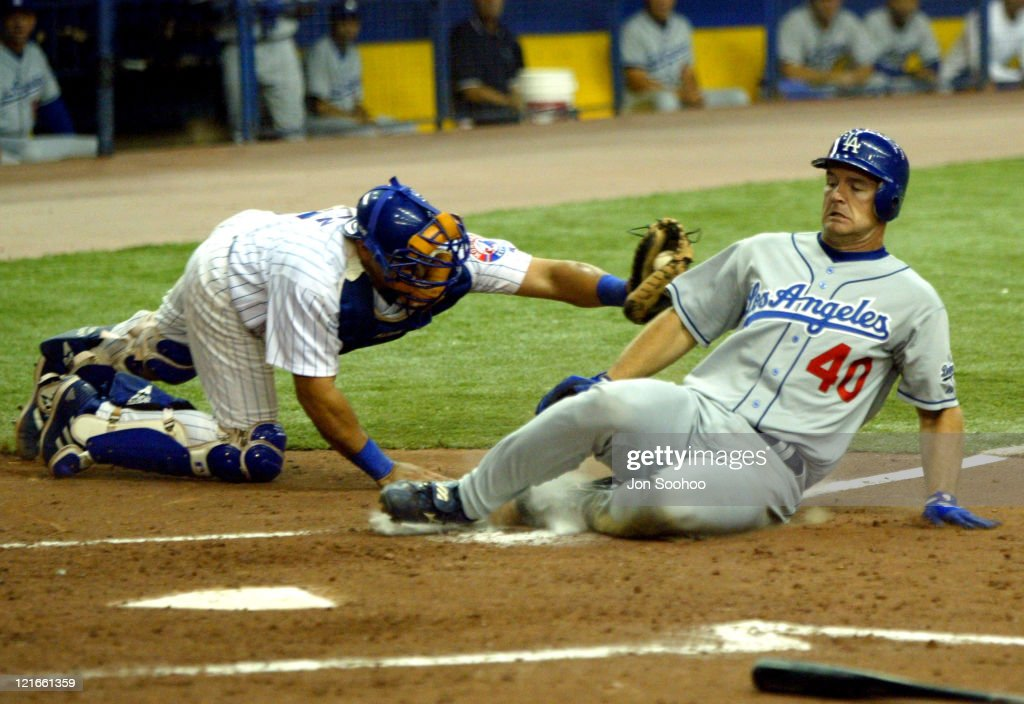 Los Angeles Dodgers <a gi-track='captionPersonalityLinkClicked' href=/galleries/search?phrase=David+Ross+-+Baseball+Player&family=editorial&specificpeople=210843 ng-click='$event.stopPropagation()'>David Ross</a> slides safely home avoiding tag of Montreal Expos catcher <a gi-track='captionPersonalityLinkClicked' href=/galleries/search?phrase=Einar+Diaz&family=editorial&specificpeople=207115 ng-click='$event.stopPropagation()'>Einar Diaz</a> in the 5th inning Tuesday, August 24, 2004 at Olympic Stadium in Montreal,Canada. The Dodgers won 10-2.