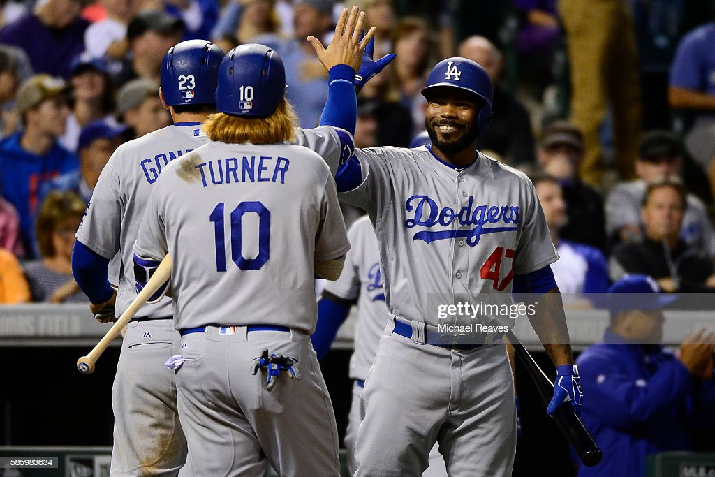 Los Angeles Dodgers first basemen Adrian Gonzalez high fives outfielder Howie Kendrick after scoring at Coors Field against the Colorado Rockies on...