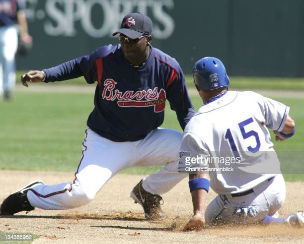 Los Angeles Dodgers infielder Rafael Furcal slides in safely beating the tag from Atlanta Braves infielder Edgar Renteria in spring training game on...