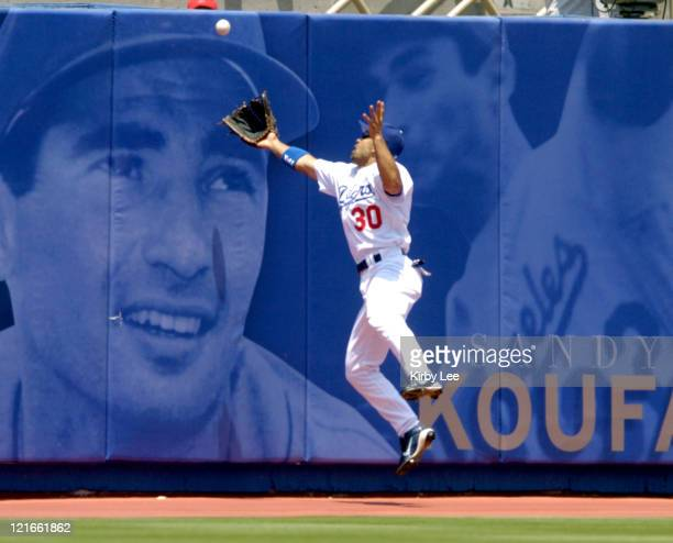 Los Angeles Dodgers left fielder Dave Roberts slams into the outfield wall after trying to catch a fly ball by Adam Kennedy of the Anaheim Angels...