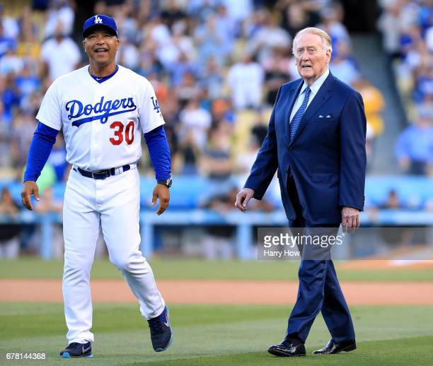 Los Angeles Dodgers manager Dave Roberts laughs as he leads announcer Vin Scully to the field during his induction into the Los Angeles Dodgers Ring...
