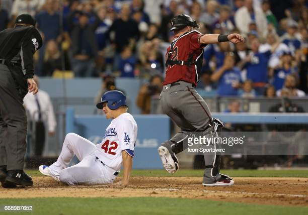 Los Angeles Dodgers Outfield Enrique Hernandez slides safely under Arizona Diamondbacks catcher Chris Herrmann on April 15 during Jackie Robinson Day...