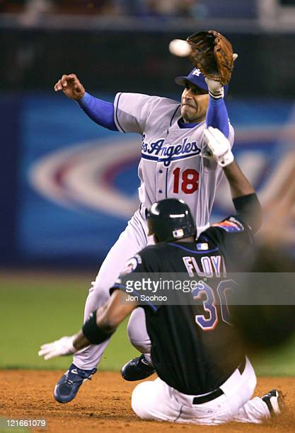 Los Angeles Dodgers' second baseman Jose Hernandez reaches for the throw as New York Mets Cliff Floyd slides under in the sixth inning August 27 2004...