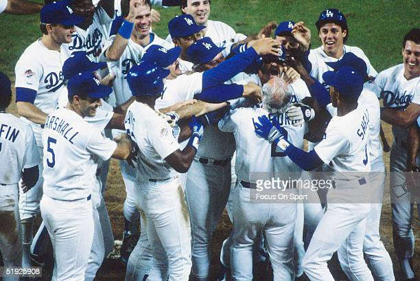 Los Angeles Dodgers teammates rush Kirk Gibson after he hit a home run against the Oakland Athletics during the World Series at Dodger Stadium on...