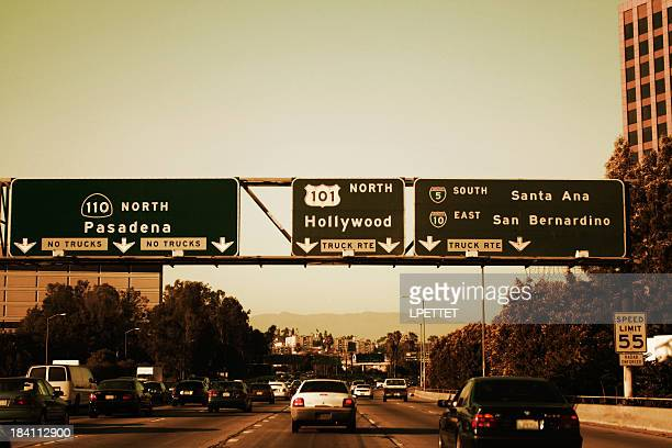Los Angeles Freeway exits on a sunny day.