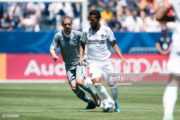 Los Angeles Galaxy forward Giovani dos Santos dribbles the ball across the field with Seattle Sounders defender Nouhou Tolo during the game between...