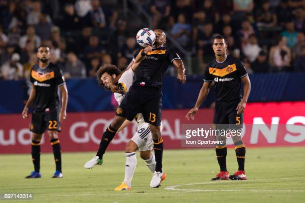 Los Angeles Galaxy midfielder Joao Pedro battles against Houston Dynamo midfielder Ricardo Clark for the ball during the game between the LA Galaxy...