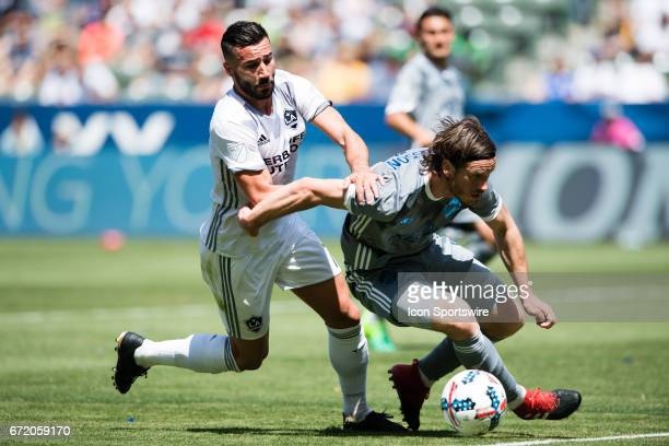 Los Angeles Galaxy midfielder Romain Alessandrini fights to get the ball against Seattle Sounders defender Gustav Svensson during the game between...